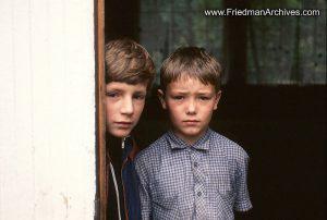 2 boys peeking around door